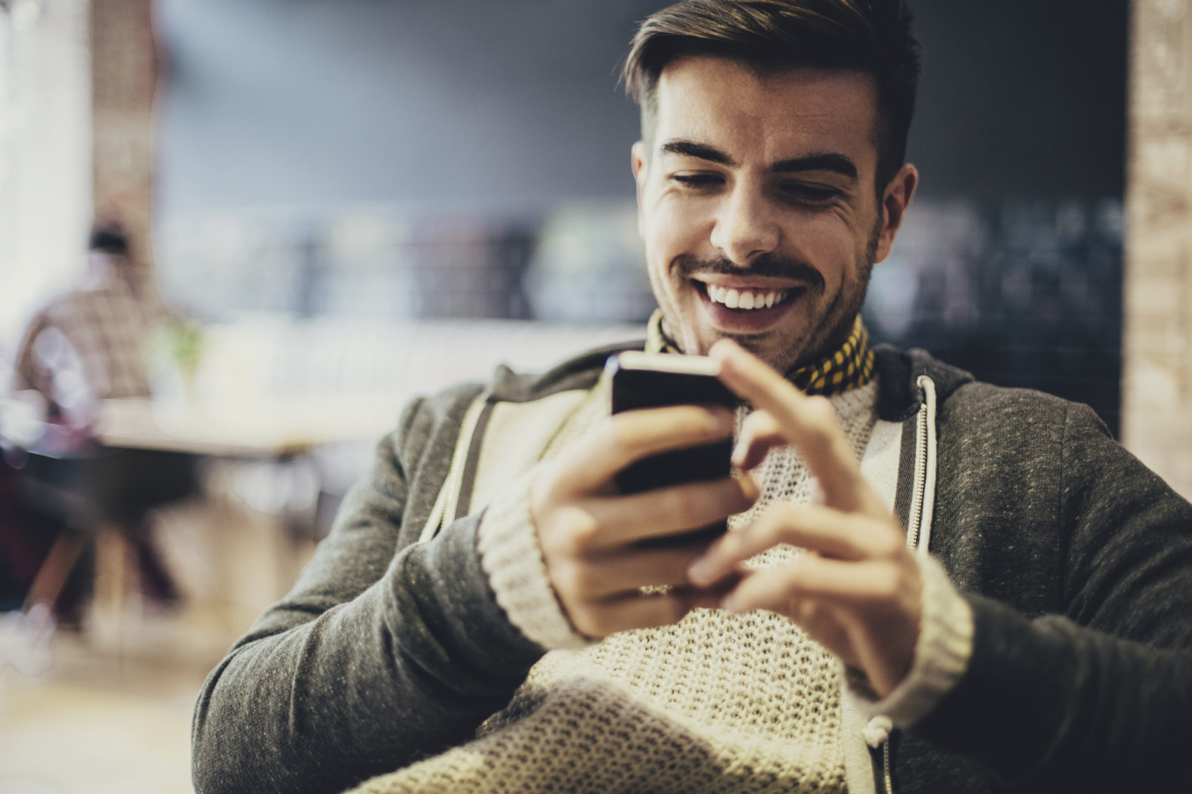 Dude smiles while looking at his smartphone